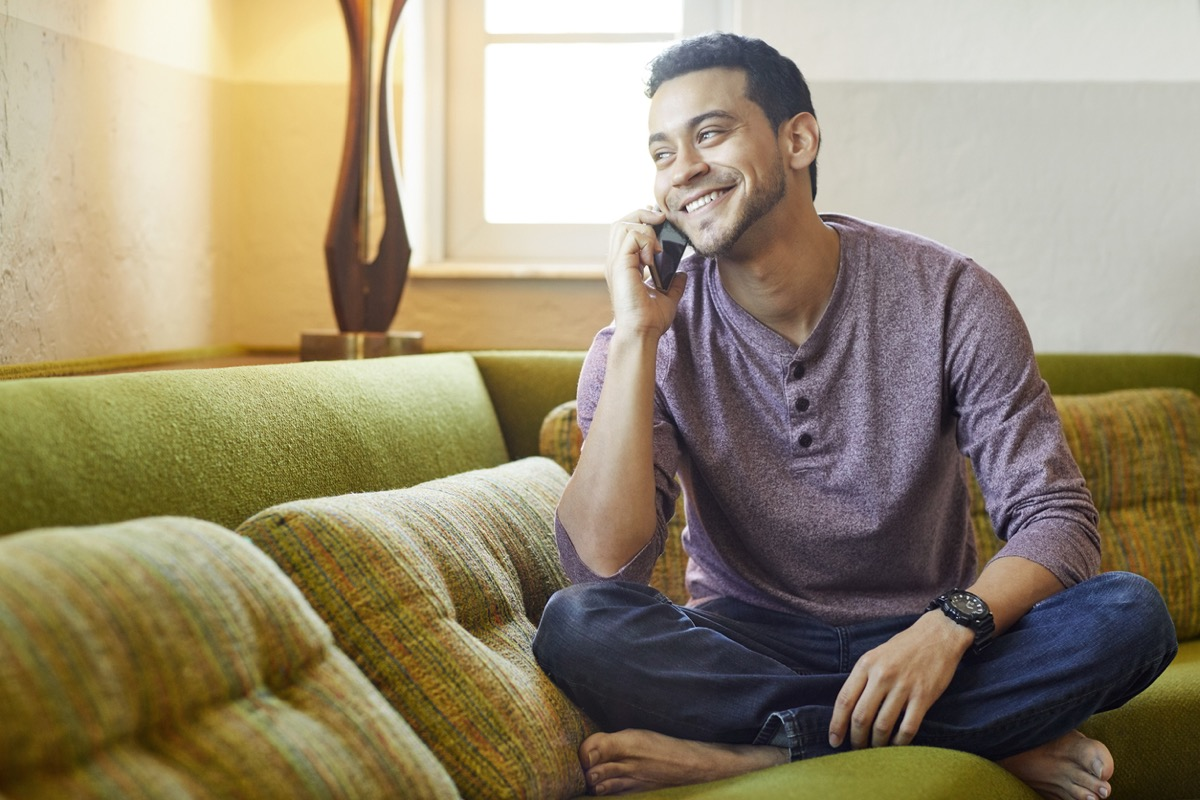 young man happily chatting on the phone on the couch