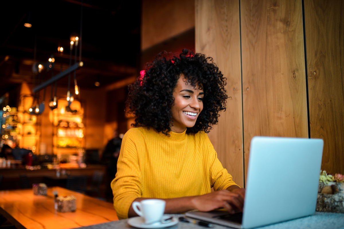 young black woman working on her laptop at a coffee shop