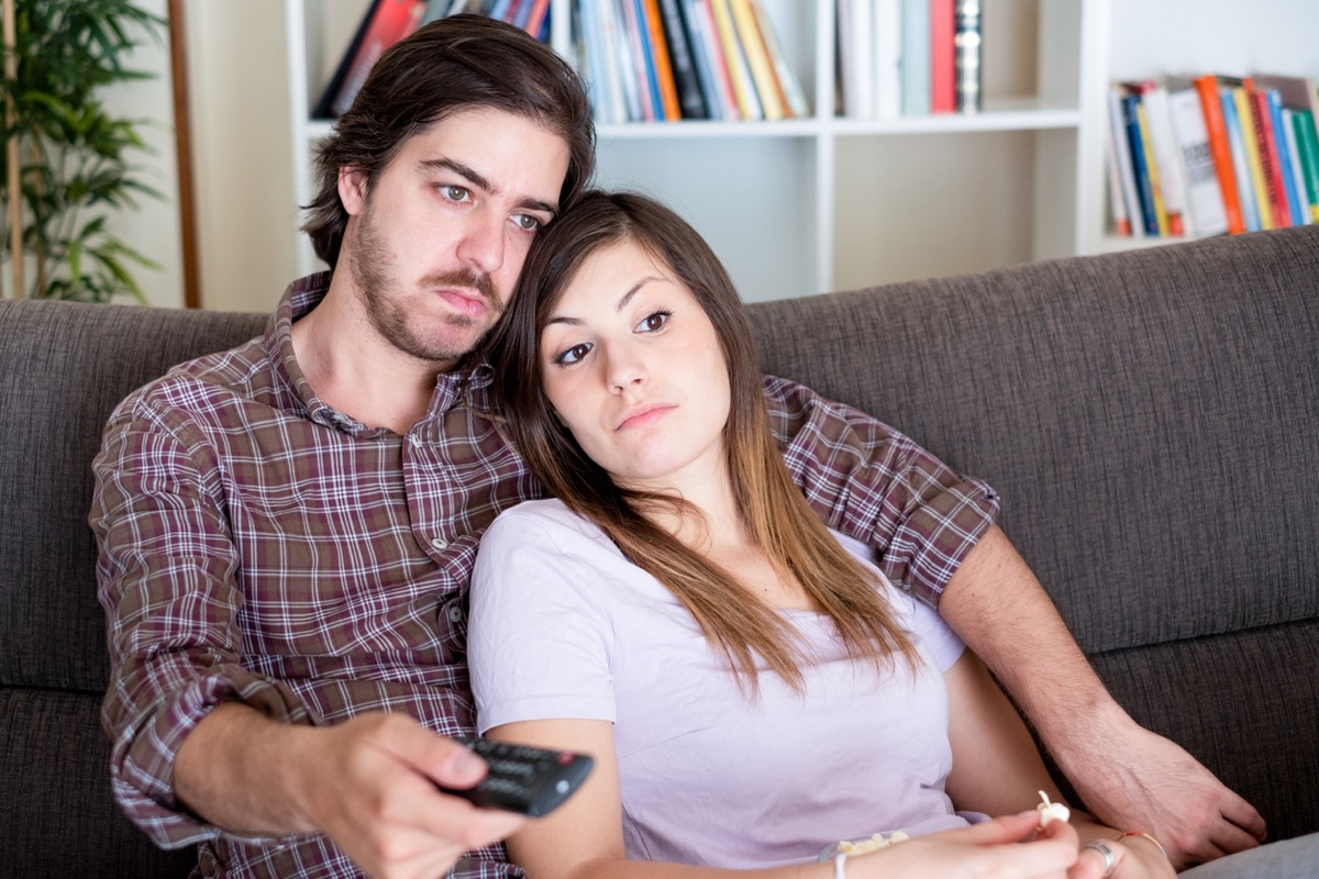 young white couple watching tv together and looking bored
