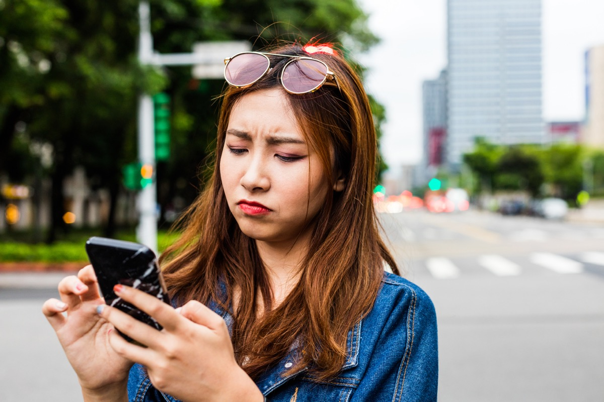 young asian woman looking disappointed while she uses her phone on the street