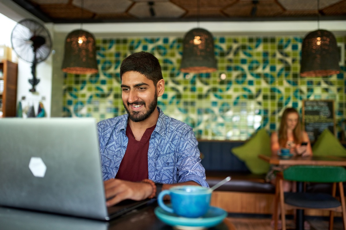 young indian man working on a laptop at a coffee shop