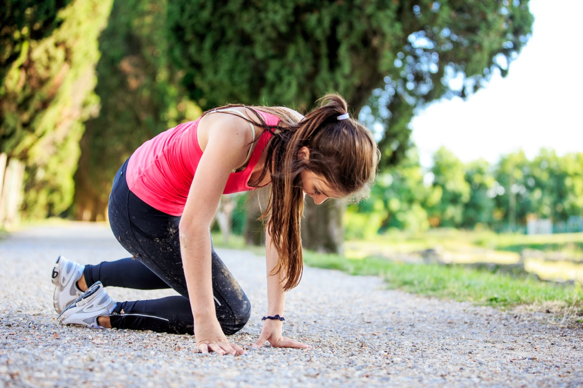 young white woman jogger getting up from the ground after falling