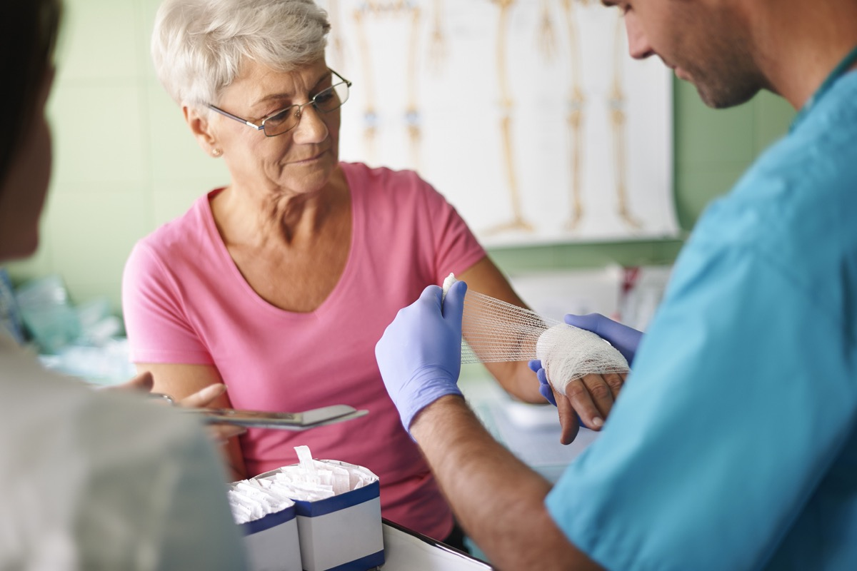 white doctor bandaging the hand of an older white woman