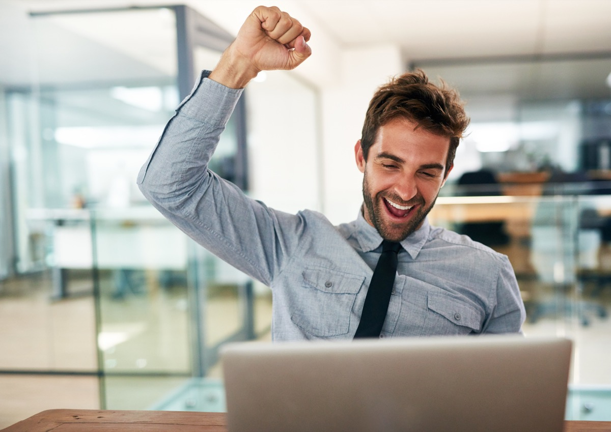 white man cheering at his laptop in an office
