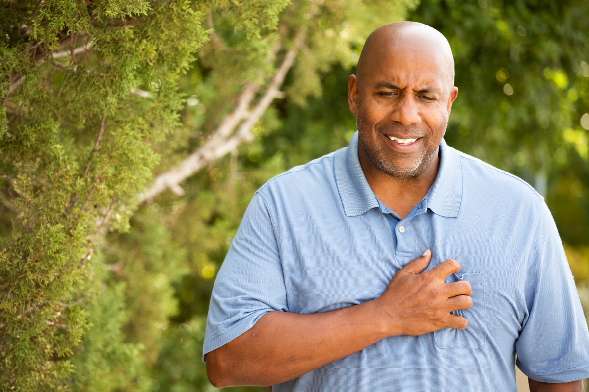 black man clutching his chest and grimacing outdoors