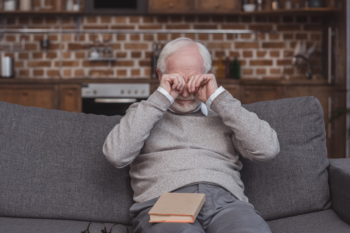 older white man rubbing his eyes on the couch