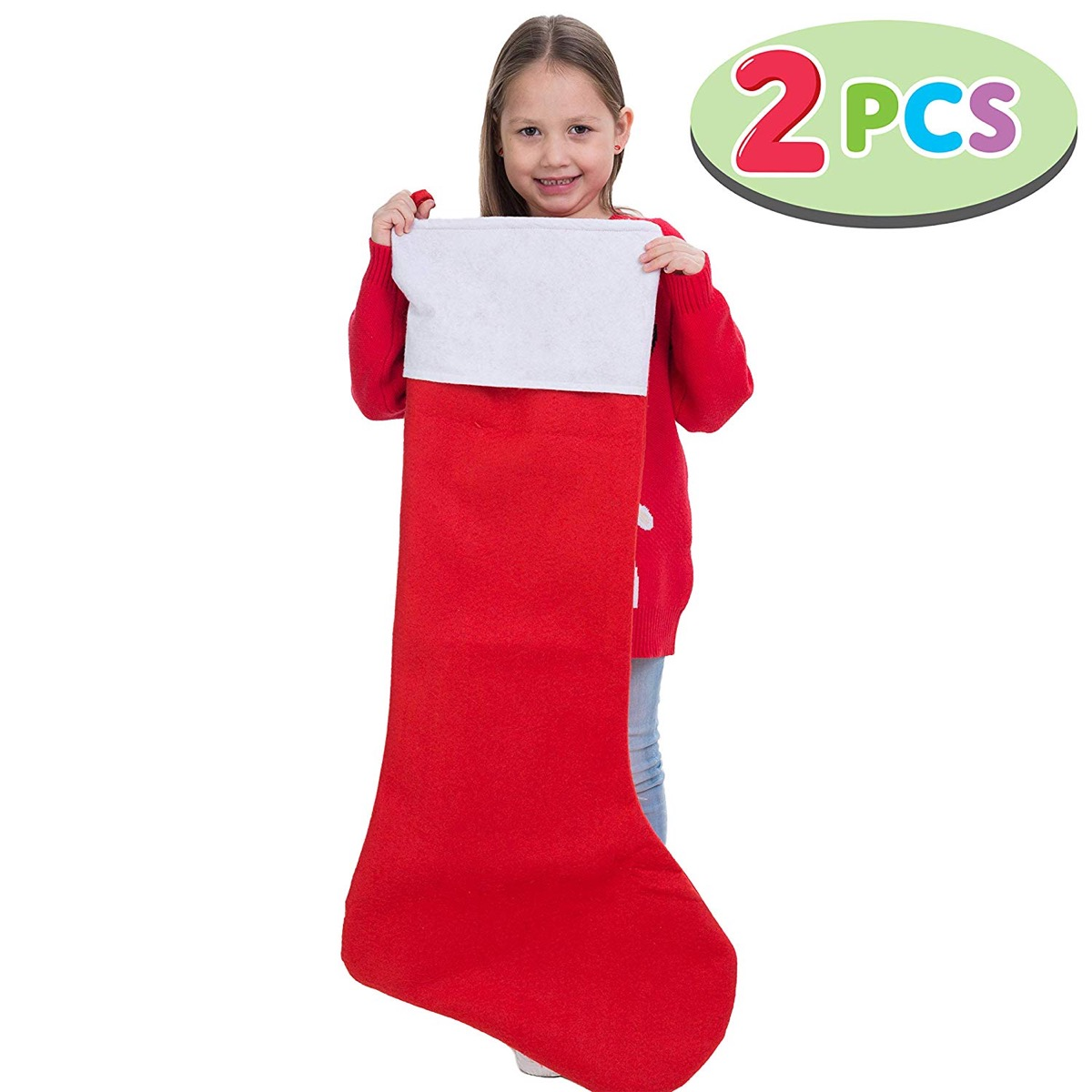 young girl holding up huge red and white stocking