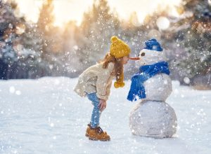 little girl outside in winter with snowman