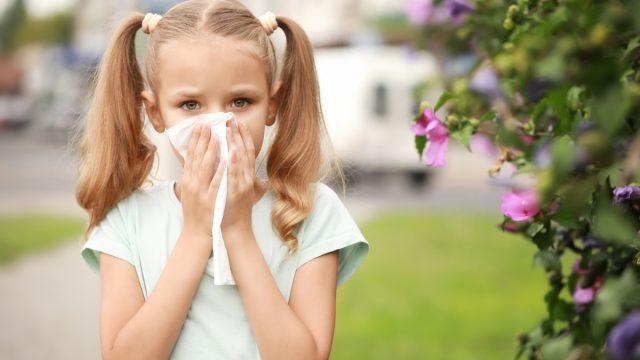 little girl sneezing outdoors