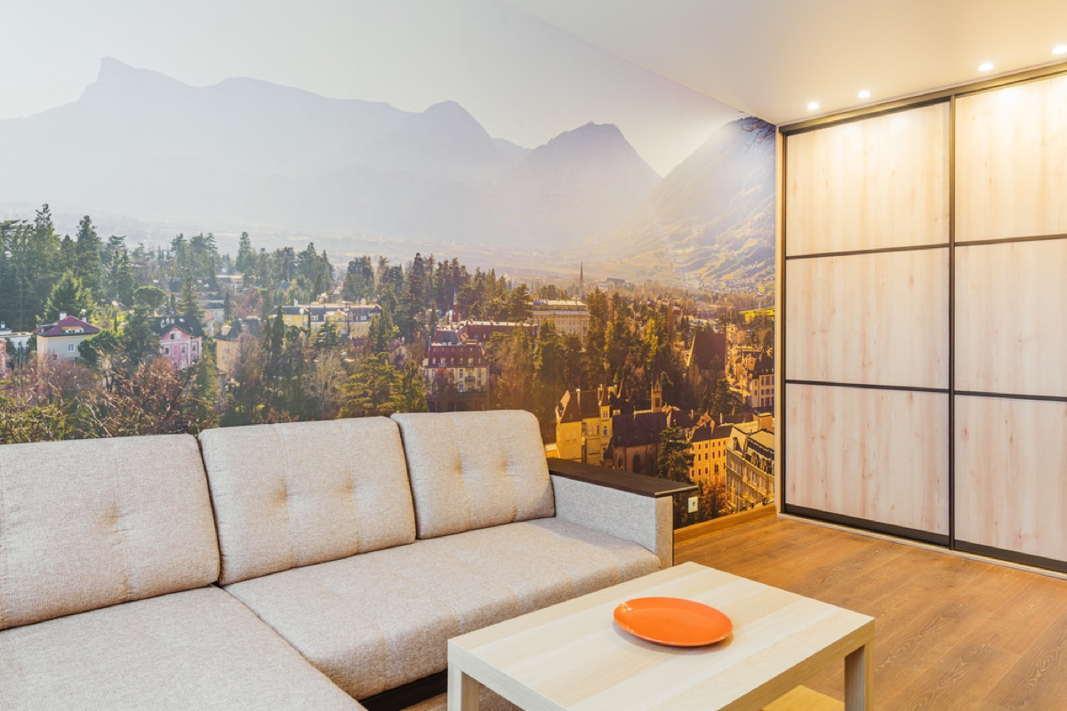 living room with cream couch and wall mural