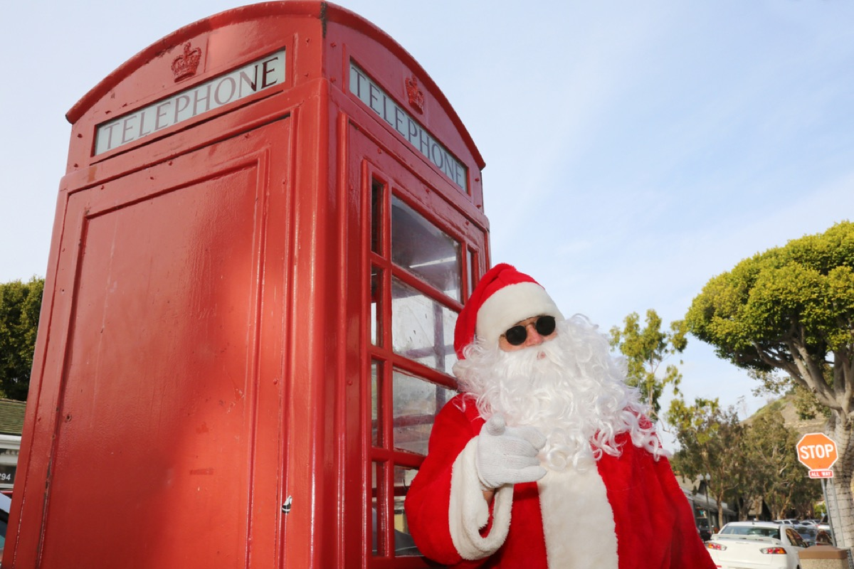 santa stands with sunglasses on at london phone booth