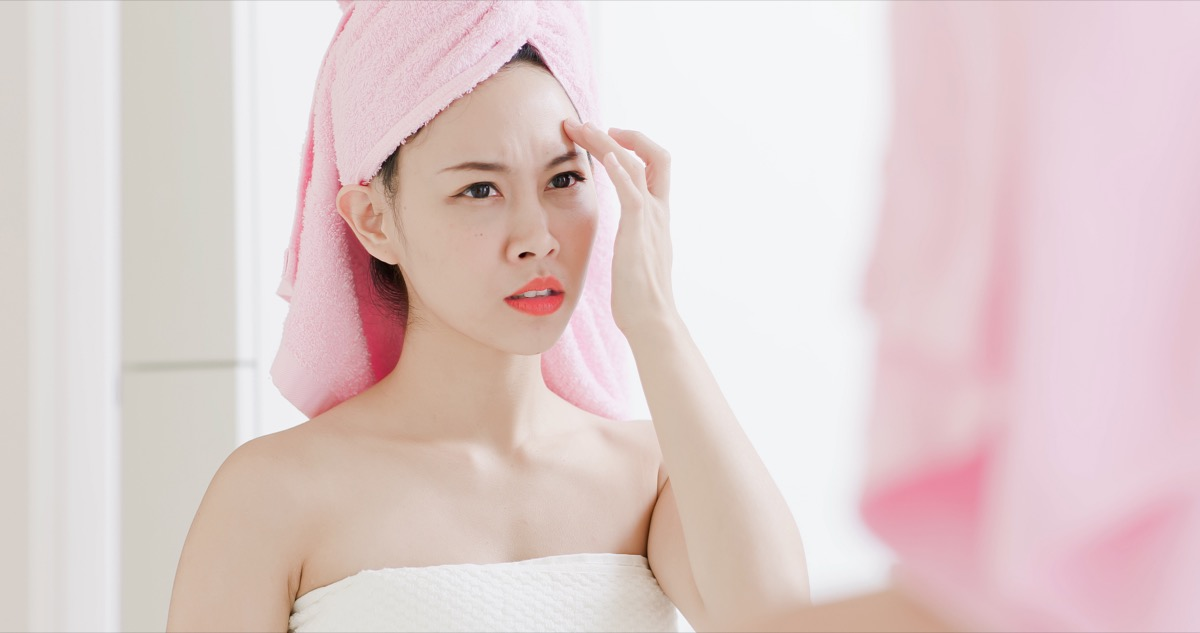 Asian woman looking at the wrinkles and blemishes on her face in the mirror