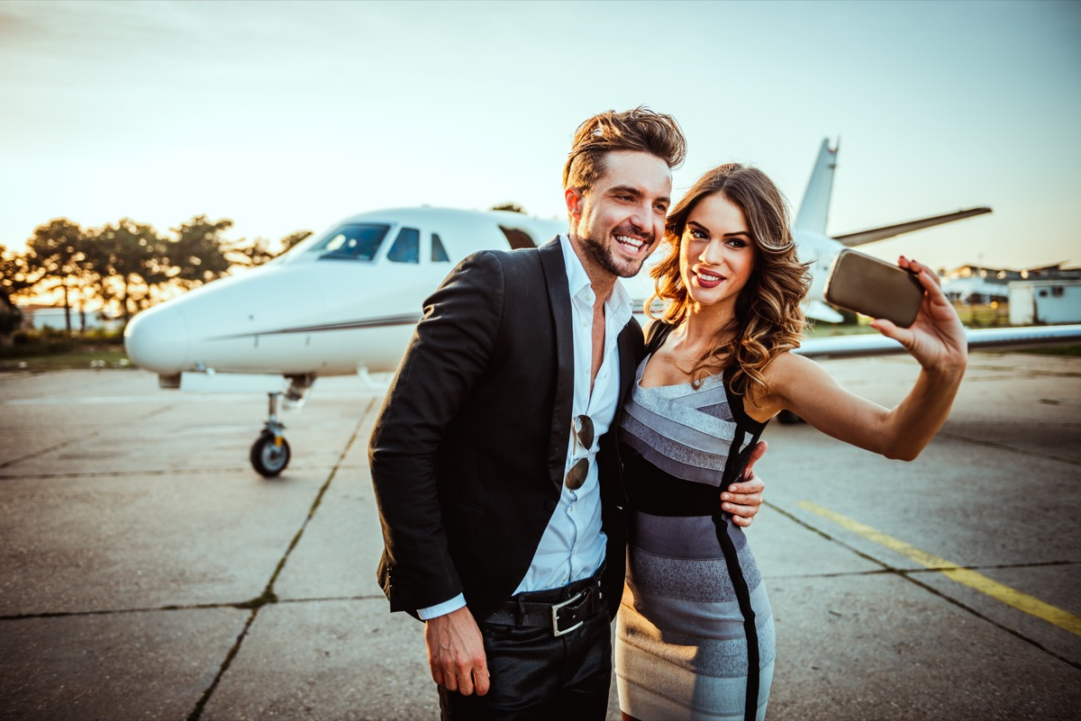 rich and famous couple taking selfie in front of private jet