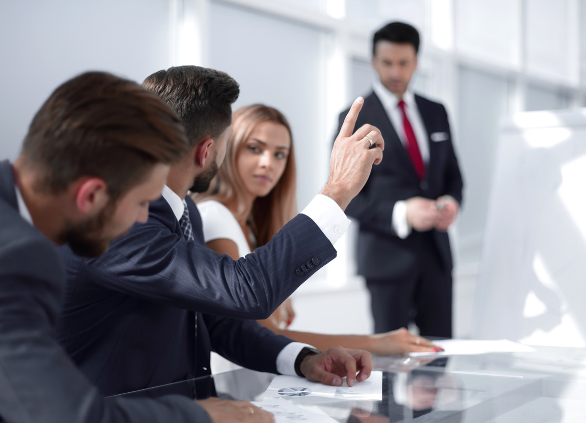 man apologizing in the workplace by raising his hand