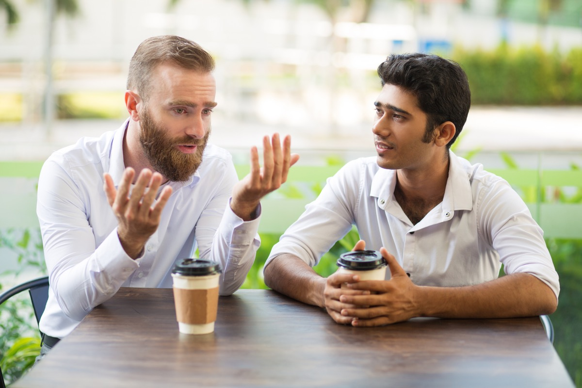 man apologizing to his friend talking while getting a cup of coffee