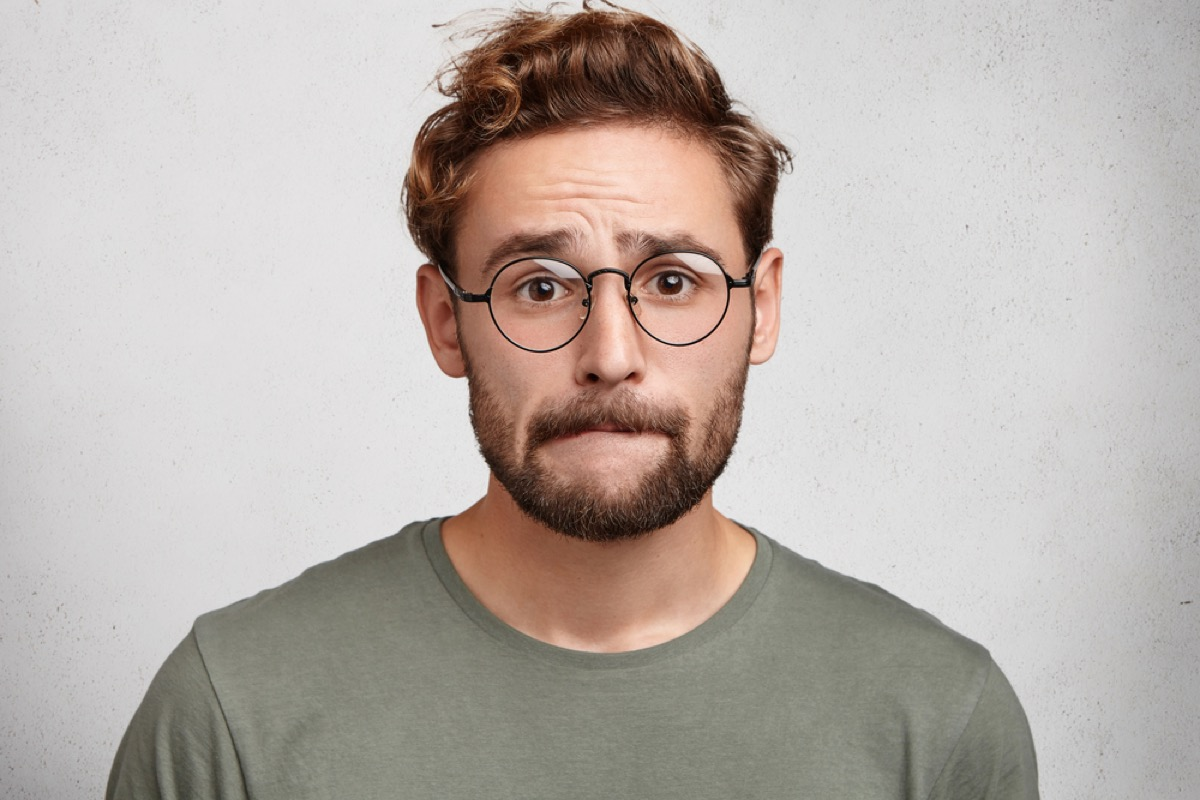 young white man with glasses biting cheek