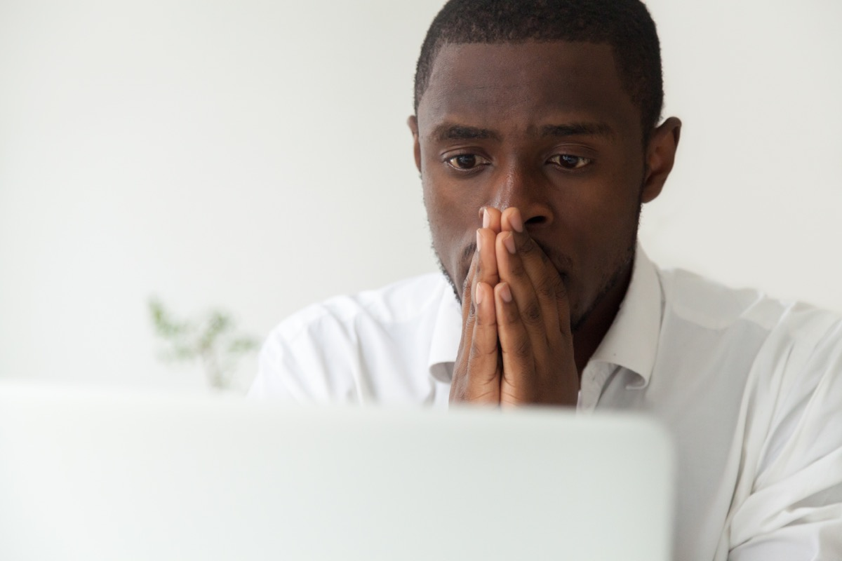 Black man sitting by his computer feeling stressed and anxious