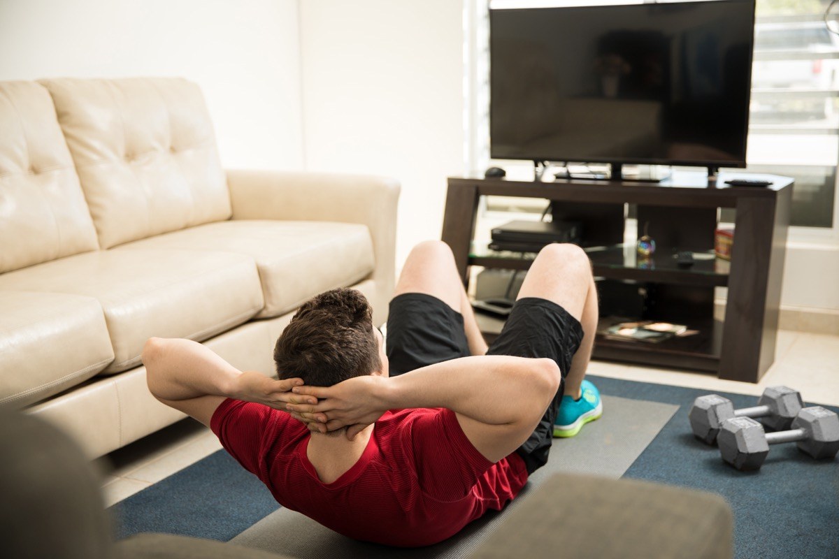 Man doing crunches in front of the TV in the living room