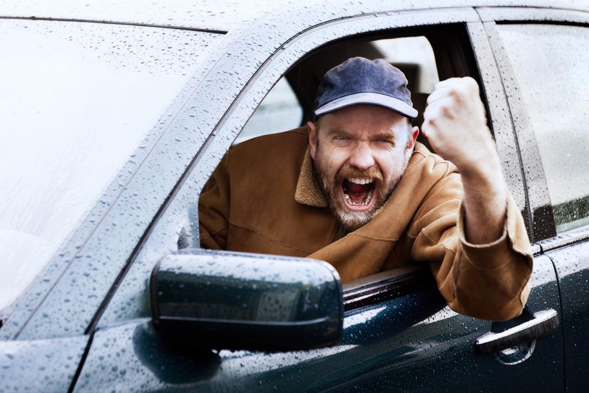 man cursing outside his car window