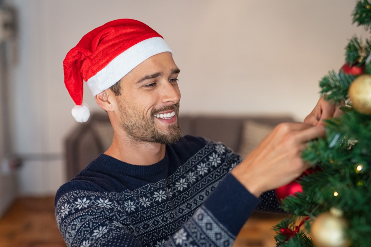 Man decorating a Christmas tree with ornaments