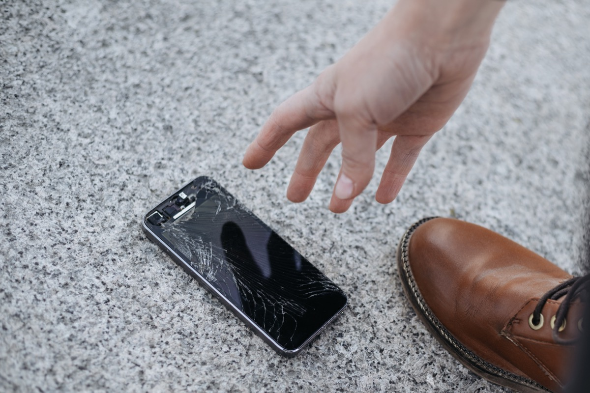 man picking up phone after dropping it on the ground
