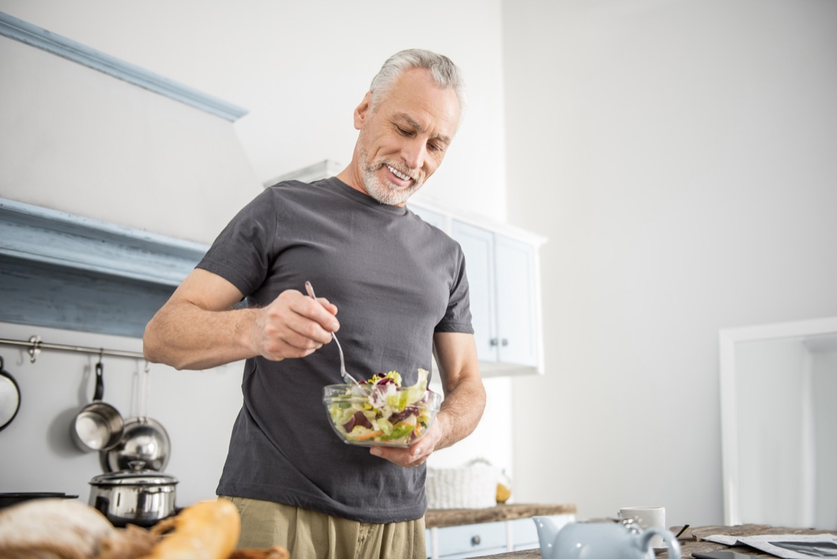 Older man eating a healthy salad in the kitchen