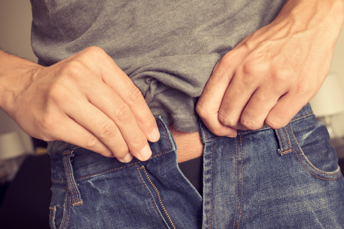 Man trying to fasten his jeans that don't fit because of weight gain