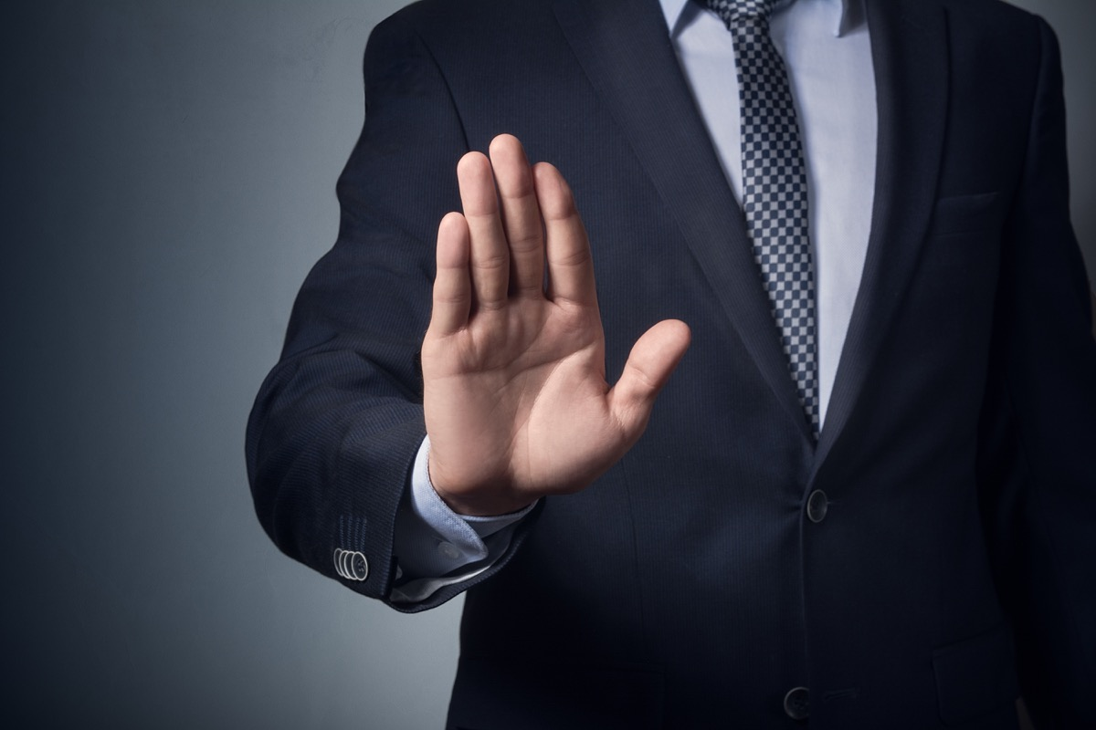 man in suit gesturing stop