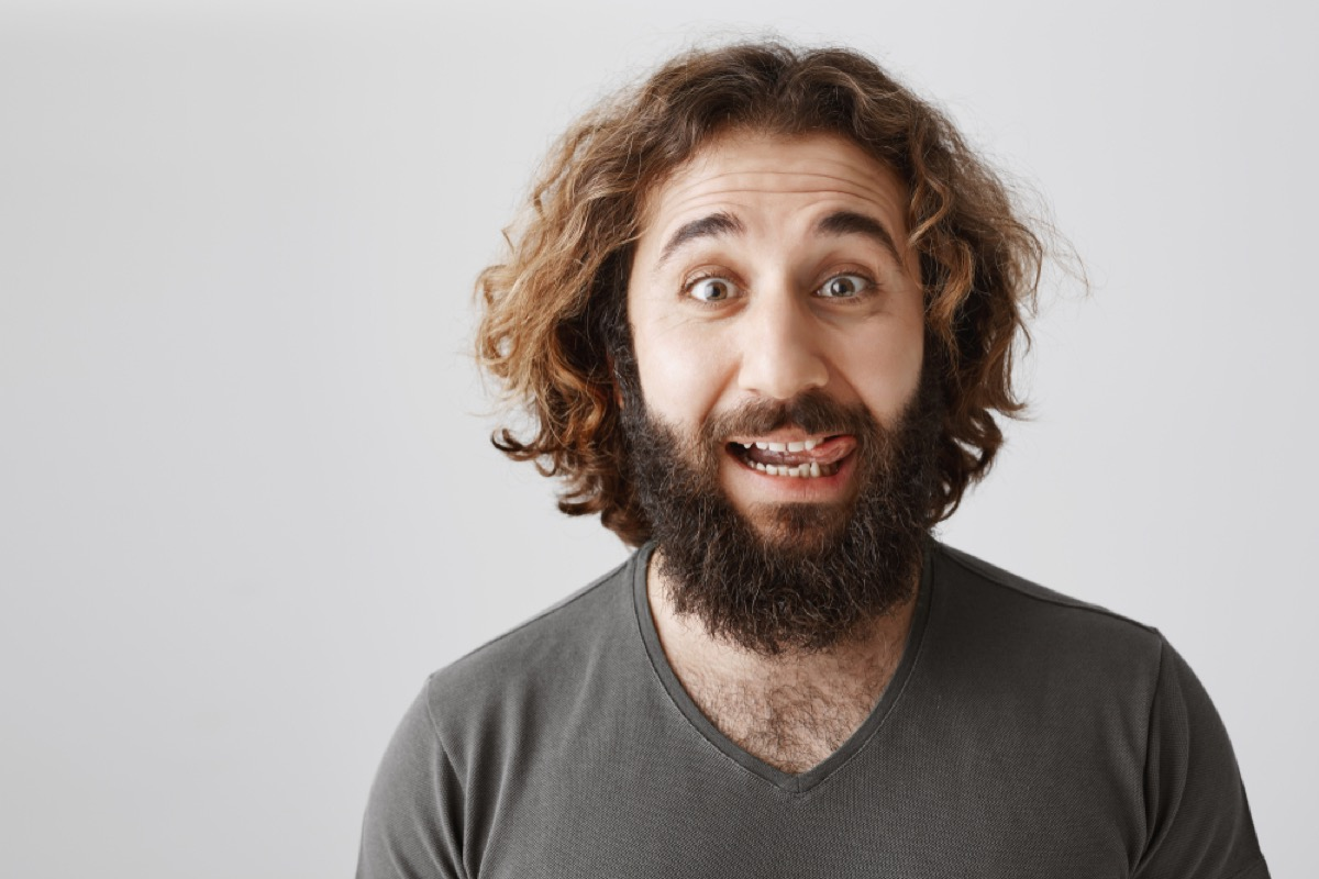 young white man with beard licking lips
