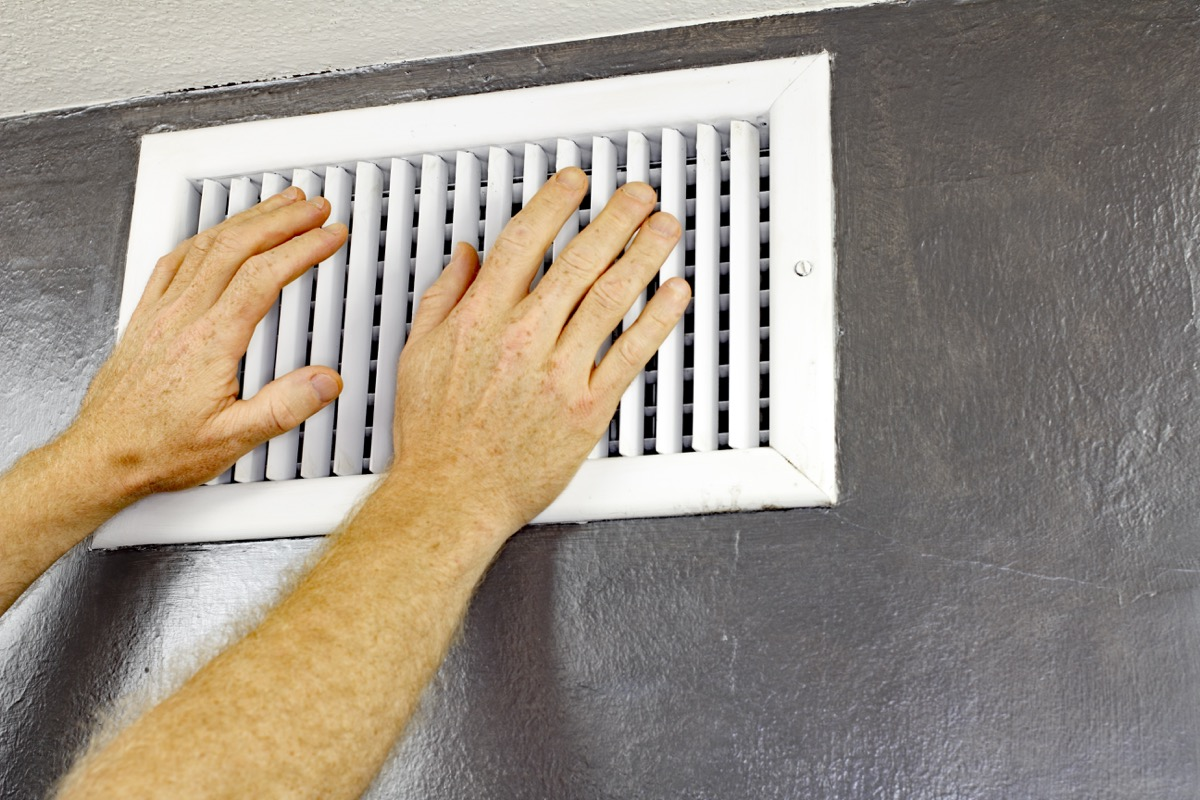 white man opening heating vent