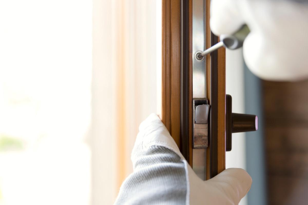man in gloves replacing wood door
