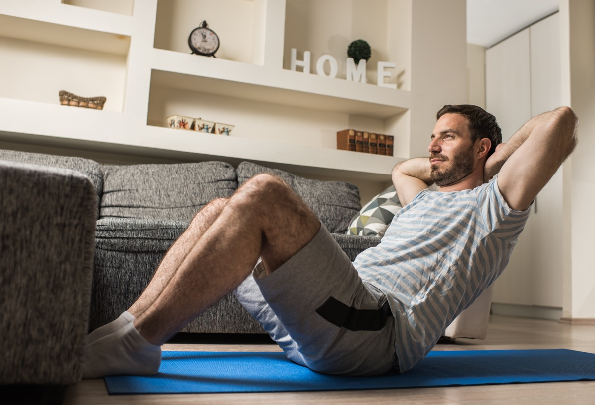 Athletic man sitting on exercise mat at home and exercising sit-ups with hands behind his head.