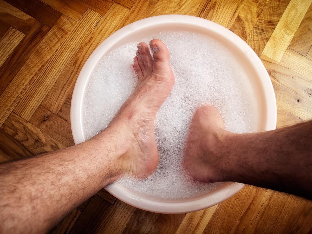 man soaking his feet in a washbowl