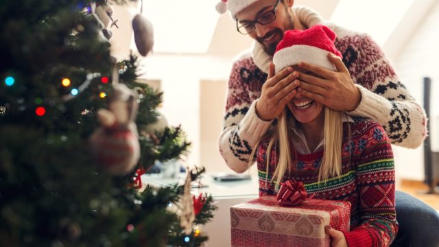 man surprising girlfriend with gifts