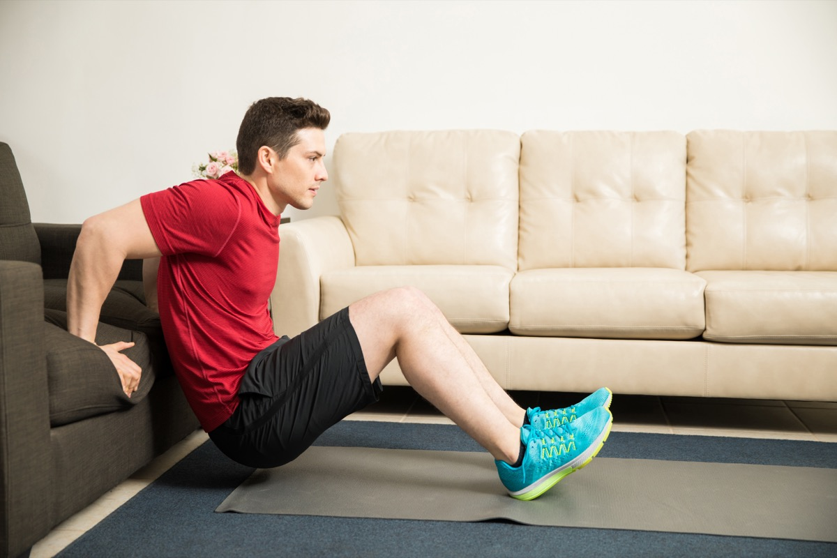 Man doing tricep dips on the couch