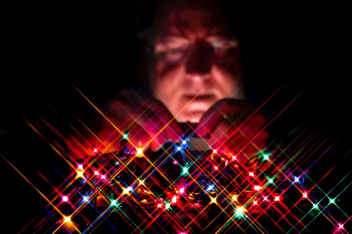 man unplugging christmas lights