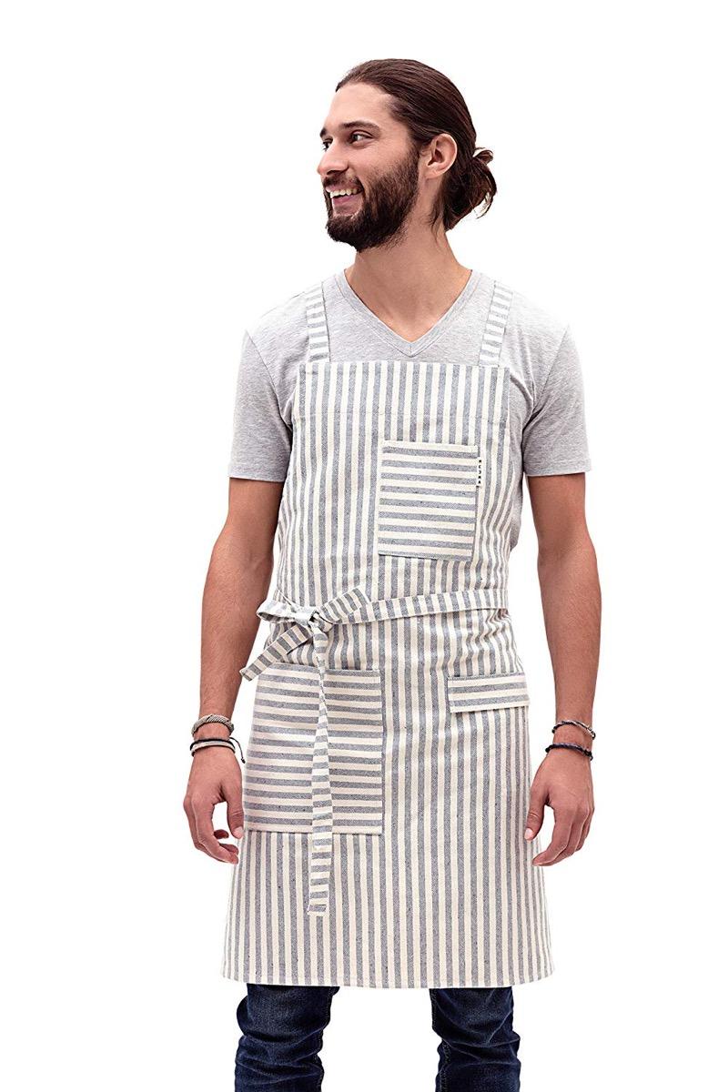 white guy with man bun in gray and white striped apron