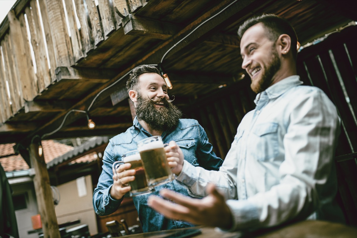 men laughing together over a beer