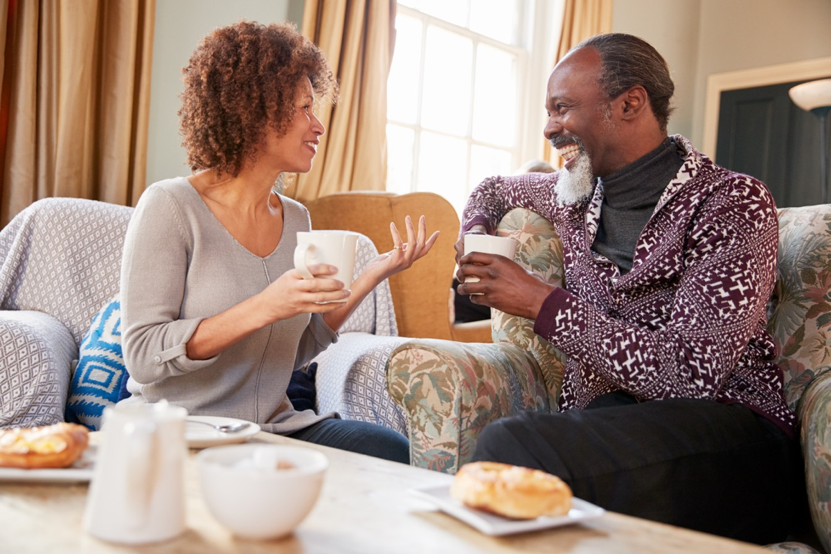 middle aged black couple talking on couch