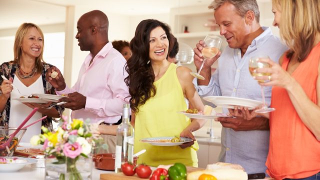 middle aged people drinking wine in kitchen at party