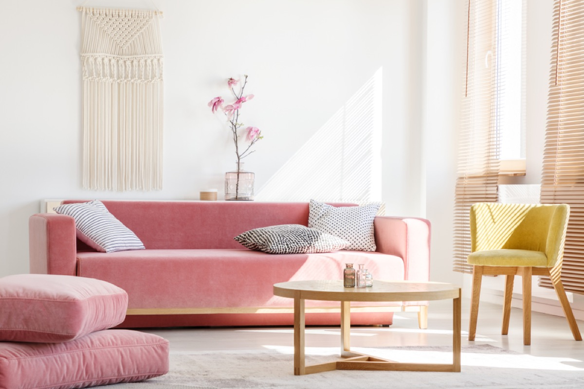 living room with pink couch and ottoman