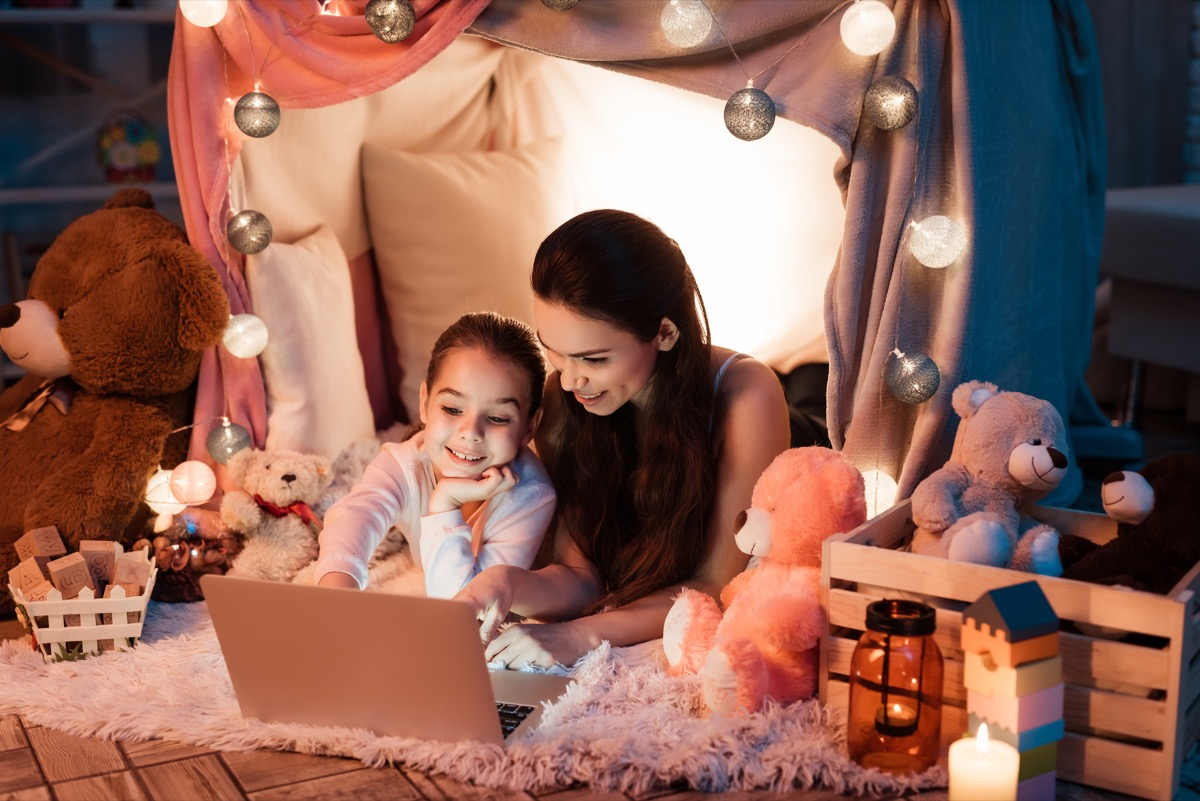 white mom and daughter watching movie in a pillow fort tent