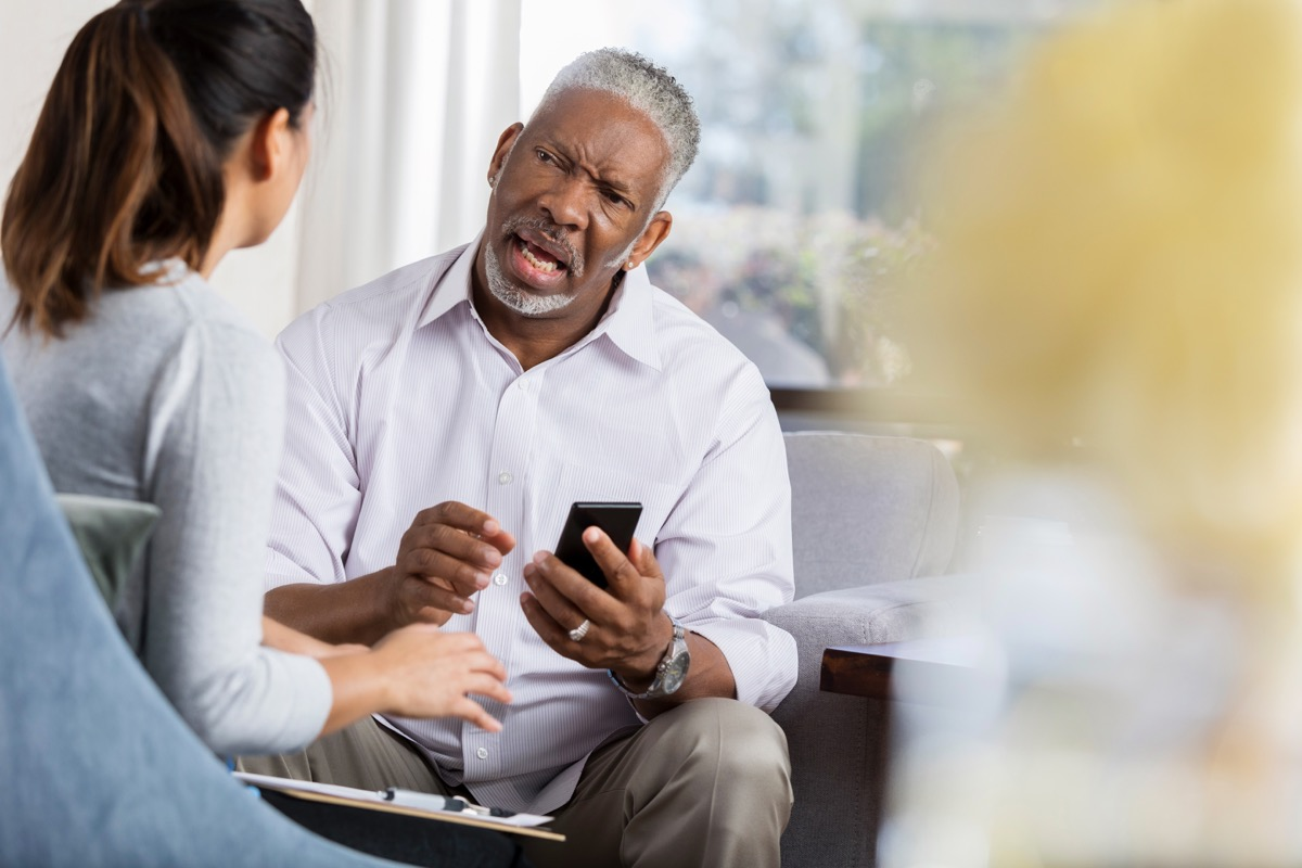 nervous man asking a female therapist for something while holding his phone