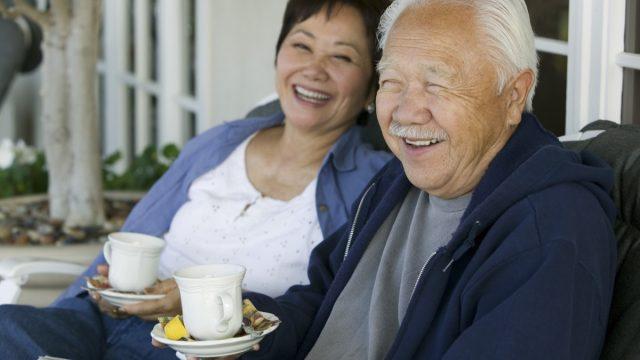 older asian couple drinking tea outdoors