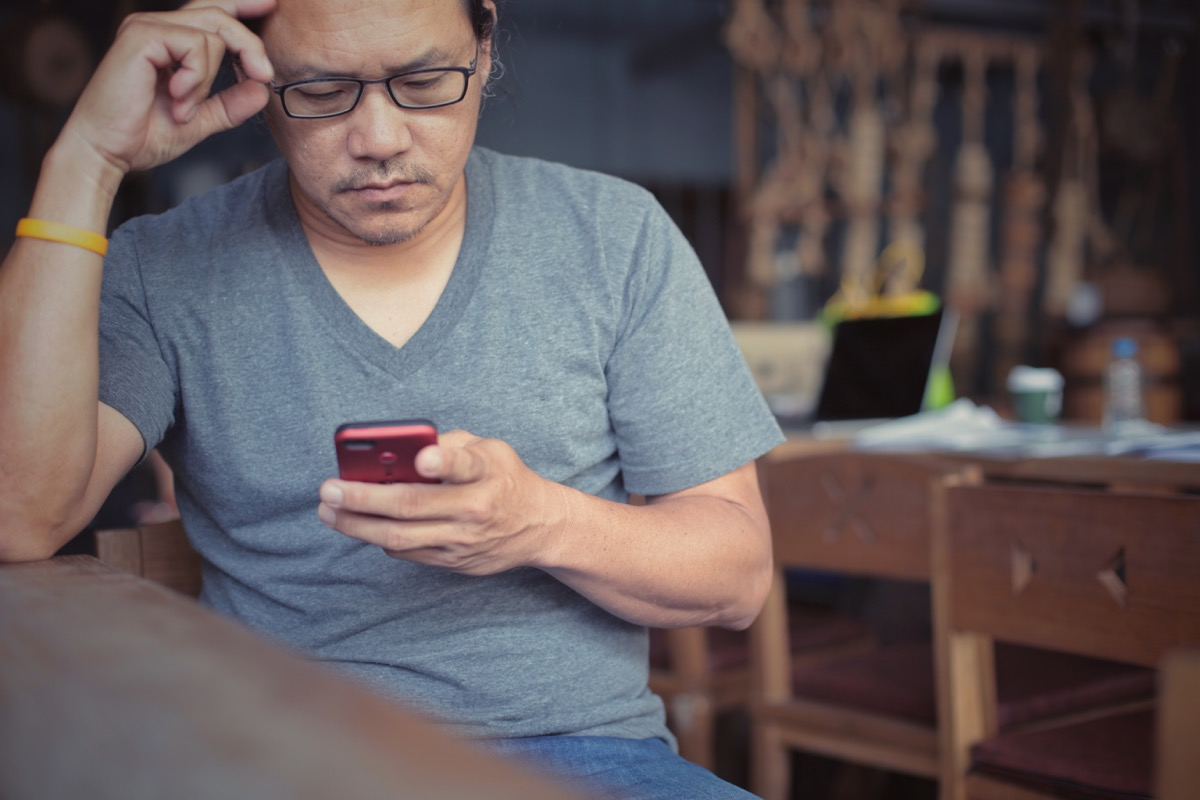 older asian man looking upset at phone