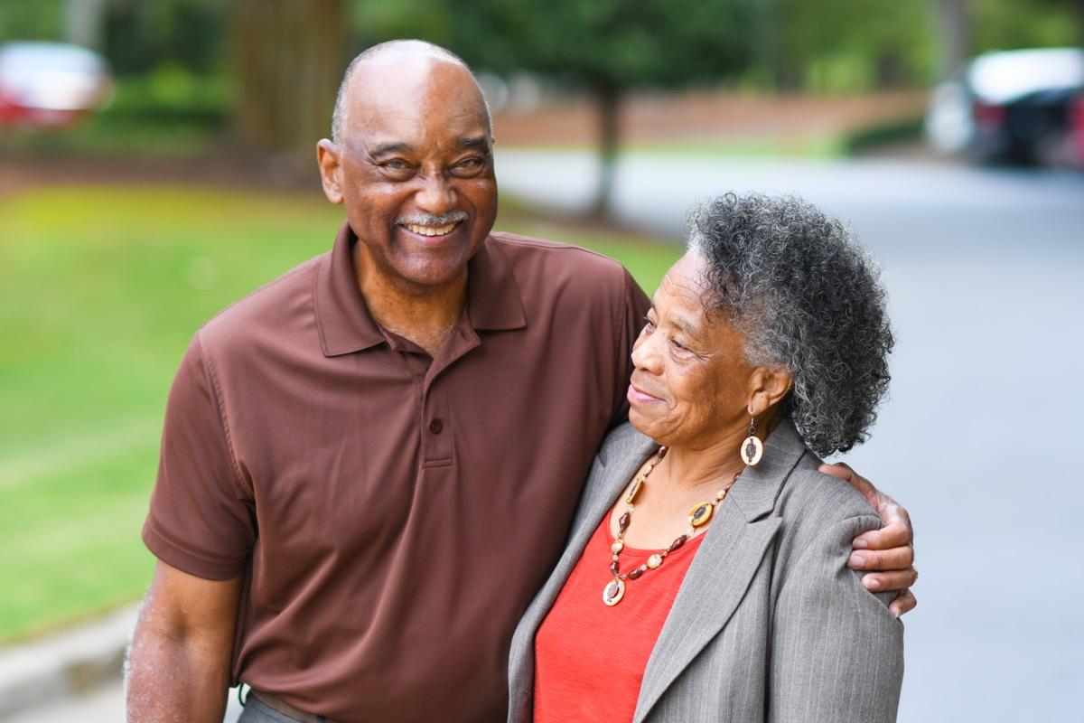 older black couple hugging outdoors
