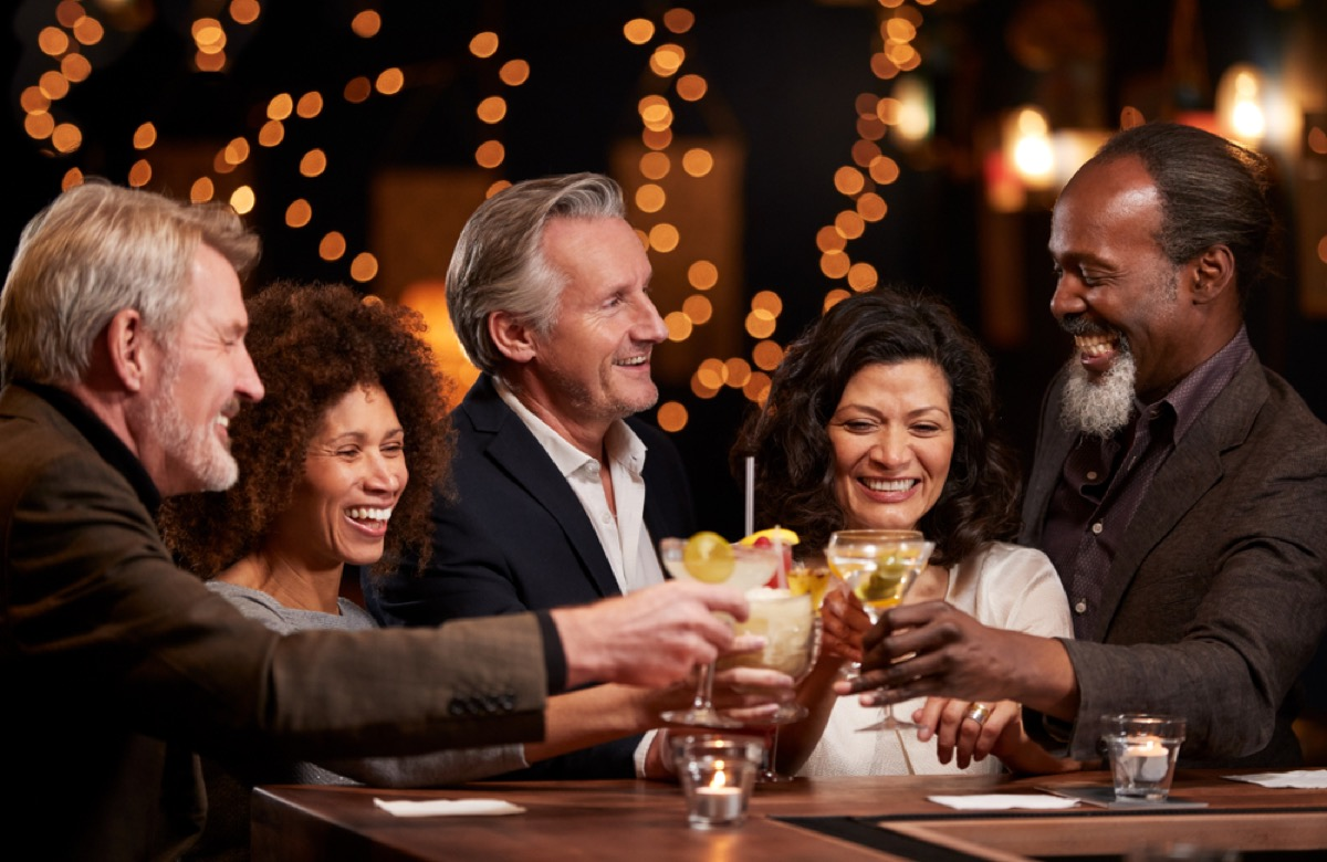 older guests of all ethnicities gather at party, toasting glasses
