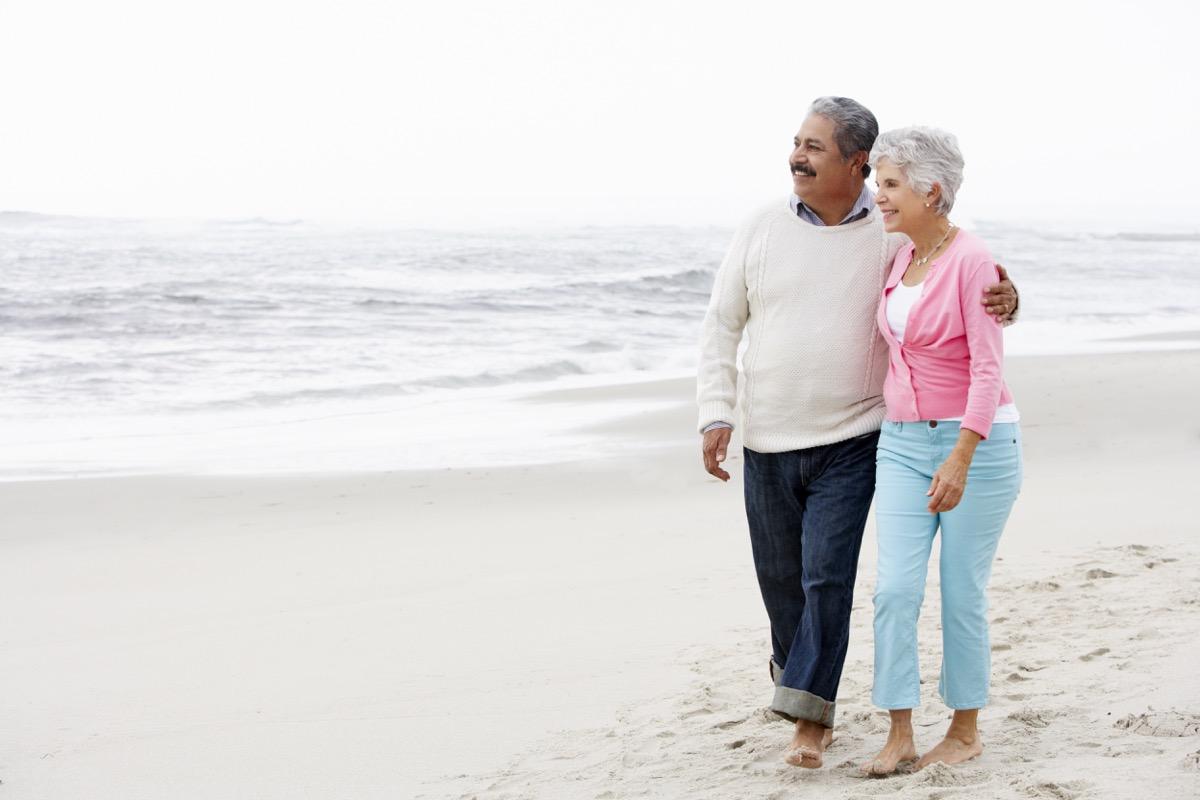 older hispanic couple walking on the beach