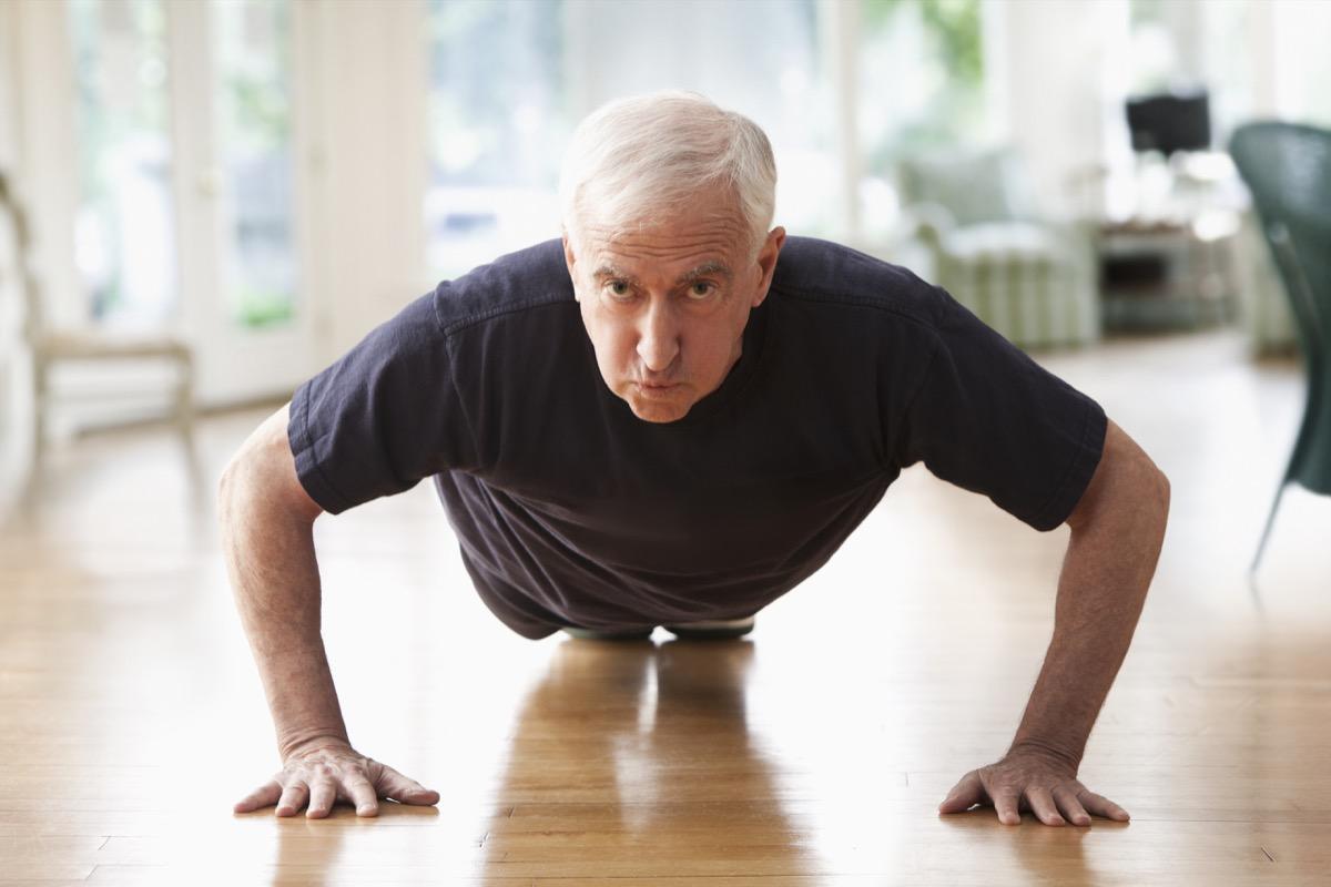 Older man doing push-ups at home