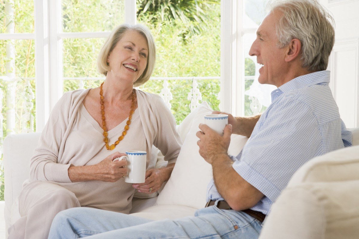 older white couple talking on couch